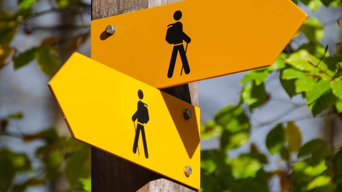 Two yellow road signs for a hiker